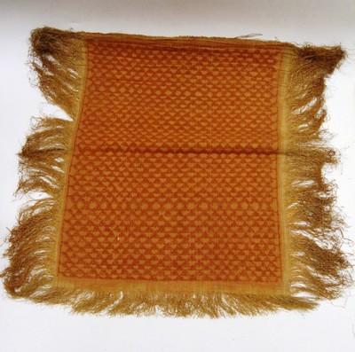 Platgeweven matje van raffia, roodbruin op een lichtere ondergrond, aan 3 kanten met franje afgewerkt. Het patroon is verkregen door suppletoire inslag, die later in het patroon is doorgesneden, waardoor een pool ontstaat. Het patroon is gevormd door 'verspringende driehoeken'.