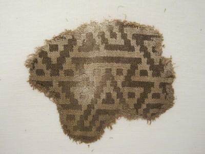 Grafgift. Een weefselfragment van wol in de kleuren bruin en beige. Op een beige ondergrond een geometrisch patroon bestaande uit trapsgewijs opgebouwde figuren. Wat aan de bovenzijde bruin is, is aan de onderzijde van het lapje beige. De grondbinding is een dubbelweefsel.