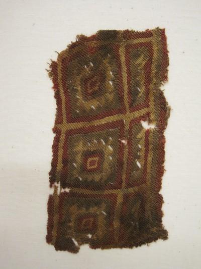 Grafgift. Een weefselfragment van lamawol in de kleuren roodbruin, geel en groen met een blokpatroon. Het patroon bestaat uit in elkaar liggende vierkanten en rechthoeken in verschillende kleuren uitgevoerd. Weeftechniek: kelim.