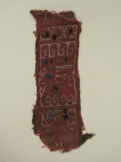 Grafgift. Een weefselfragment van wol en katoen in de kleuren roodbruin, bruin, oker, beige en blauw. Een roodbruine ondergrond met ingeweven blokjes in verschillende kleuren en erop geborduurde dunne lijntjes in diverse patronen. Aan beide kanten van het fragment zitten franjes.