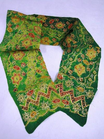 Twee techniekvoorbeelden van de prada jumputan, met goud beschilderde afgebonden doeken: groene ondergrond met geel, rood en oranje bloemmotieven in dwarsbanen (a); bruin-oranje ondergrond met veelkleurige rozetbloemen en sterretjes. De rand in donkere tinten(b).
