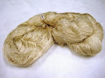 Vier techniekvoorbeelden van songket en limar: streng witte zijde (a); streng zijde na afbinding (ikat) en verving in rood, oranje, groen, paars en zwart (b). De bindsteken zijn al losgehaald. Japans goudgaren (c); een stukje songket (goudweefsel) (d). Van de twee strengen zijde worden heup- en schouderdoeken gemaakt (Kain limar); het goudgaren wordt geïmporteerd uit Singapore voor de vervaardiging van goudweefsels; het stukje songket komt van een oude doek, oude doeken worden vaak in stukjes gescheurd om het waardevolle gouddraad eruit te halen en opnieuw te kunnen verwerken.