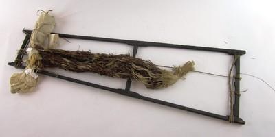 Ikatraam, tangga, (a) van ijzerhout, aan elkaar gebonden met rotan reepjes. Hierop zijn tot schering gewonnen vezeldraden (b) gespannen, wit vezelmateriaal, afgebonden met lembah (c), het bruine vezelmateriaal, en aan het raam zit dan ook nog een stukje geweven stof (d), een deel van de omwikkelingen is niet bruin maar naturel (vermoedelijk om het verschil in verfkleur aan te geven). Op het ikatraam worden de tot schering gewonnen vezeldraden gespannen om te worden afgebonden met lembah, het bruine vezelmateriaal. Dit wordt stevig om de vezeldraad gewikkeld en aan het eind met een knoopje vastgebonden; de vrij lange uiteinden worden niet afgesneden. Het vezeldraad ziet er vervolgens uit zoals op het raam te zien is. Het patroon hierop is bedoeld voor een vrouwenrokje (ulap).