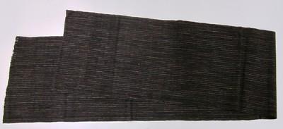 Streepweefsel van hand gesponnen katoen, linnenbinding in blauw, rood en naturel op een zwarte ondergrond. De doek heeft de kleuren blauw, rood en zwart, synthetisch geverfd. Motieven: ular serit: de rups die jeuk veroorzaakt, streepjes in rood-blauw-rood en wit met wit (de rups ?) op zwart. Deze stof is bestemd voor de vervaardiging van een mannenjak. De doek is vermoedelijk een erfstuk (simpenan), en maakte deel uit van een bruidsgift (sasrahan).