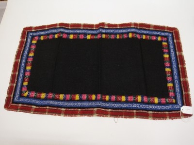 Donkerblauw kleedje met 3 geborduurde randen in de kleuren geel, rood, groen, paarsrood en paarsblauw.