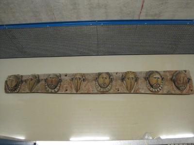 Voorgevel van een ceremonieel huis bestaande uit grote houten balken met uitgesneden koppen die de Yamgeesten voorstellen en vele met geestessymbolen beschilderde panelen van sagopalmblad.