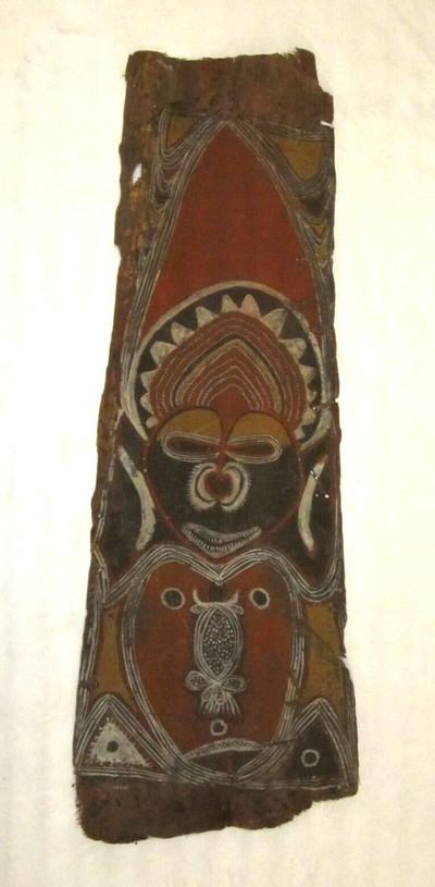 Langwerpig stuk sago palmblad, aan één zijde beschilderd in zwart, rood , wit en geel, met onder andere een mensengelaat met een hoofdtooi. Het stuk is onderdeel van de versiering van een huis.