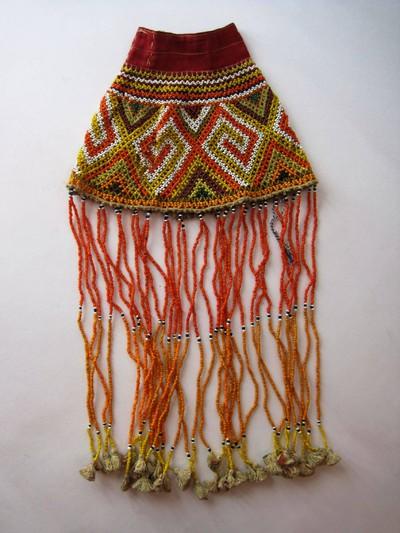 Kandaure bestaande uit een mouwvormig kraalwerk, veelkleurig, van boven afgewerkt met een rood katoenen band. Langs de onderzijde lopen lange strengen met kralen, eindigend in kwastjes. De Kandaure is een hoornvormige kraalwerk versiering met lange franjes van kralen. Ze worden gemaakt door de Sa'dan Toraja en gebruikt bij begrafenissen en levensbevestigende ceremoniën. De kandaure wordt gebruikt bij dodenfeesten: aan een lange stok bij de lijkkist neergezet. Als het lijk tijdens de rouwplechtigheden verplaatst wordt, gaat ook de kandaure mee. Vrouwelijke verwanten dragen de kandaure op de rug met de franjes gevouwen voor op de borst. Zij begroetten de begrafenisgasten. Ook de danseressen bij begrafenissen dragen deze versieringen, bijvoorbeeld tijdens de gellu' dans of bij dansen voor ceremoniën voor het oosten, de Maro rijst rituelen. Mannen rijgen de kandaure aan een touw dat op een bamboe vuikvormige staketsel is bevestigd. Het begin is meestal een stuk stof dat geweven is met de kaartband techniek. In het kraalwerk is het gebalde vuisten motief aangebracht, dat sekong wordt genoemd. Ook zijn bovenin antropomorfische figuren te herkennen. Oude Kandaures worden gezien als kostbare erfstukken die beschermen tegen ongeluk en die soms zelfs een naam hebben. Kandaures worden verbonden met bepaalde oude huizen en kunnen door anderen geleend worden. Het object symboliseert overdaad, zoals een hoorn des overvloed.