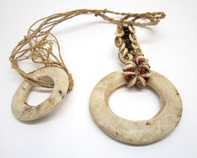 Sieraad bestaande uit een ronde ring van geslepen schelp (tridacna), met hieraan een stuk touw waarop schelpjes en gekleurde kraaltjes zijn aangebracht. Aan het uiteinde van het touw nog een kleinere, ronde ring van schelp.