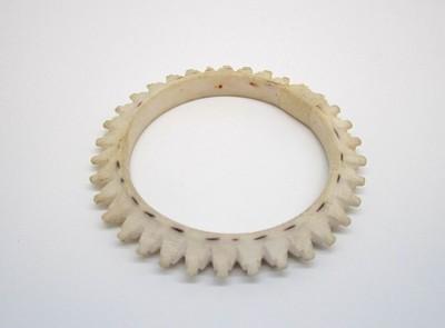 Sieraad bestaande uit een ronde ring van schelp, eruit ziende als een tandwiel, waarschijnlijk op machinale wijze voorzien van gekartelde punten.