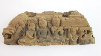 Een reliëf met de voorstelling van 3 zittende figuren.