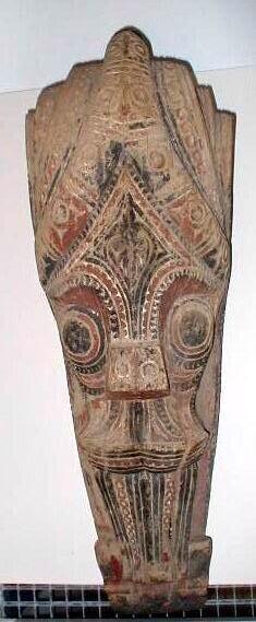 Ornament voor bevestiging aan een huis voorstellende een Singa met twee grote bolvormige ogen, uitstulpende neus en van opzij bewerkt in volutenachtige ornamenten; resten van rode, zwarte en witte polychroom. De Singa heeft een onheilafwerende, beschermende functie.