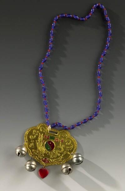 Amulet van goudkleurig blik in de vorm van een slot. Op het amulet staat centraal in rood en groen het jin-jang teken en aan weerszijden daarvan in relief een draak en een griffioen. De rand is geheel bezet met de dieren uit de chinese astrologie. Onderaan het plaatje hangen vier bellen met in het midden een rood plastic hartje. Het amulet hangt aan een ketting van blauwe en rode plastic kraaltjes. Dergelijke amuletten werden voornamelijk bij kinderen omhangen teneinde ze hiermee aan het leven vast te ketenen.
