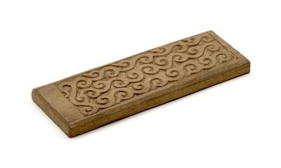 Rechthoekige plank met een grof uitgesneden versiering van krulmotieven. De gesneden rand is niet van gelijke breedte.