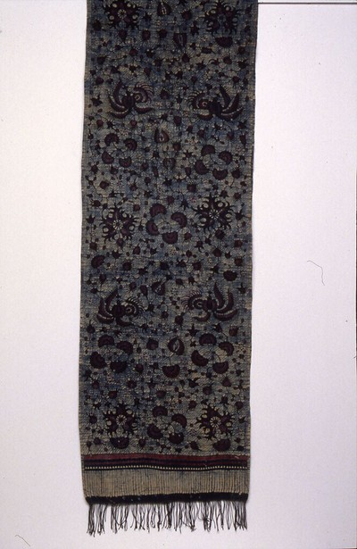 Handbatik op hand gesponnen, handgeweven katoen. De doek heeft de kleur pipitan: rood (synthetisch) en blauw (natuurlijk, indigo, oververving met zwart. Motieven: laseman: bloemen en vogels in Chinese stijl, in rood en blauw op een lichte achtergrond met blauwe stippellijnen. De franje is wit/blauw gevlekt (tahi lalat, vliegenpoepjes) met brede geknoopte randen (krawangan). Kemada aan de korte zijden. Langs de zelfkant is een rode draad geweven. Schouderdoek voor getrouwde vrouwen met kinderen uit het centrumdorp.