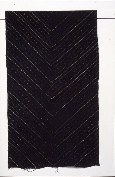 Handbatik op hand gesponnen, handgeweven katoen. De doek heeft de kleur irengan: wit op blauw, natuurlijke indigo. Motieven: kembang jeruk: diagonale lijnen van kleine bloempjes. De stof werd vervaardigd om er een driekwart broek, een sruwal, voor een bruidegom van te naaien. Zo'n broek is onderdeel van de salin manten, het kostuum dat gedragen wordt tijdens de laatste fase van het huwelijksritueel, wat aangeeft dat de drager nu gehuwd is. Het fijne witte motief stelt de geurige oranjebloesem voor en geeft evenals de kleurcombinatie (donkerblauw met wit) bescherming bij risicovolle ondernemingen, en is bij uitstek geschikt voor een bruidegom.