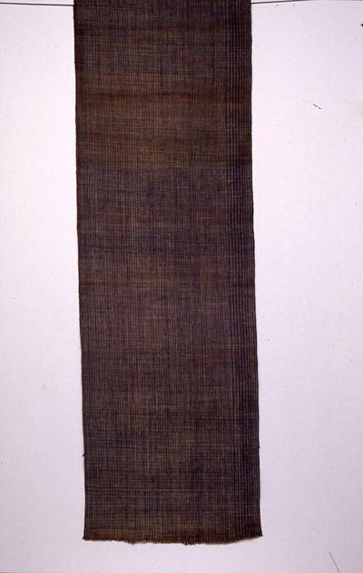 Weefsel van hand gesponnen katoen in naturel, helderblauw en helderrood; bijzondere scheringtechniek. De doek heeft de kleur blauw, natuurlijke indigo, en helderrood, synthetische verving en naturel. Motieven: intip hiyan (mat om rijst uit te laten dampen): een blokjespatroon ontstaan door de scheringtechniek. Aan het weefsel geen zelfkantafwerking. Dit weefsel is bestemd voor de vervaardiging van een onderlijfje voor de traditionele vroedvrouw (dukun bayi) of dorpsomroeper (kebayan).