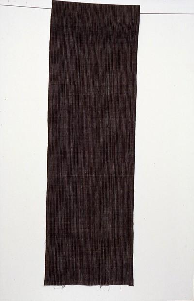 Streepweefsel van dik hand gesponnen garen in scheringtechniek in zwart/rood en naturel bloemetjes. De doek heeft de kleuren zwart en rood, synthetisch geverfd. Motieven: kembang manggar: bloesem van de pinangpalm, geen zelfkant, aan een kant een witte eindafwerking, streep in wit-rood op zwart. Deze stof is bestemd voor de vervaardiging van kleding (jas of broek) voor een bruidegom. Deze doek is daar nooit voor verwerkt. Het is een erfstuk en is jarenlang bewaard geweest. De doek maakt deel uit van een bruidsgift. # Soms wordt dergelijk familiebezit in steeds kleinere stukken geknipt en doorgegeven aan de jongere generaties.
