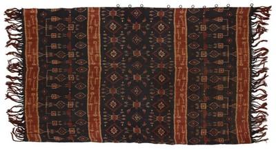 Grove ikatdoek van katoen (gemaakt voor toeristen), twee banen in de lengte aan elkaar genaaid. Motieven: schedelbomen en dieren en in het middendeel geometrische figuren. De randen zijn niet gefitst, de franje niet getwijnd. De doek heeft de kleuren bruin, rood en crème.