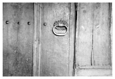 Iron door knocker with sun ornamented base on the wooden door