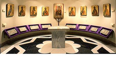 Μουσείο Ιεράς Μονής Κύκκου (Κύπρος): Άποψη της κόγχης στην αίθουσα 2 του Μουσείου της Ιεράς Μονής Κύκκου. Στο κέντρο δεσπόζει μαρμάρινη παλαιοχριστιανική τράπεζα, ενώ γύρω είναι τοποθετημένα μαρμάρινα παλαιοχριστιανικά ανάγλυφα (πιθανώς επιστύλιο). Ψηλότερα, στο μέσο, βρίσκεται μεγάλη λειτανευτική εικόνα της Θεοτόκου Οδηγήτριας (13ος αιώνα). Εκατέρωθέν της είναι τοποθετημένες εικόνες με Αποστόλους, έργα του Παύλου Ιερογράφου (17ος αιώνας).