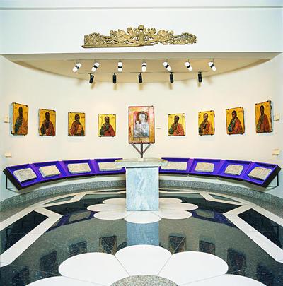 Μουσείο Ιεράς Μονής Κύκκου (Κύπρος): Άποψη της κόγχης με τη μαρμάρινη παλαιοχριστιανική τράπεζα στο τέρμα της αίθουσας 2 του Μουσείου της Ιεράς Μονής Κύκκου. Γύρω είναι τοποθετημένα μαρμάρινα παλαιοχριστιανικά ανάγλυφα (πιθανώς επιστύλιο). Ψηλότερα, στο μέσο, δεσπόζει μεγάλη λειτανευτική εικόνα της Θεοτόκου Οδηγήτριας (13ος αιώνα). Εκατέρωθέν της εκτίθενται εικόνες με Αποστόλους, έργα του Παύλου Ιερογράφου (17ος αιώνας).