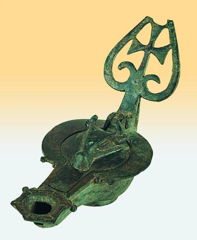 Μουσείο Ιεράς Μονής Κύκκου (Κύπρος): Λύχνος του οποίου η λαβή κοσμείται με σταυρό εγγεγραμμένο σε καρδιόσχημο διάτρητο φύλλο και το πώμα με βουκράνιο (Δ 145)