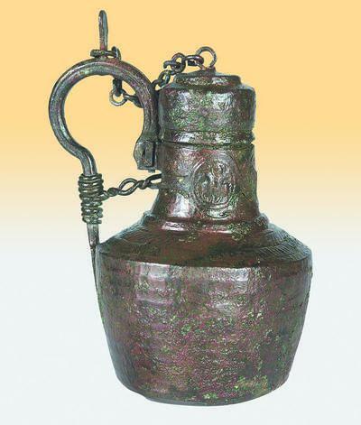 Μουσείο Ιεράς Μονής Κύκκου (Κύπρος): Ορειχάλκινο σφυρήλατο αγγείο με λαβή και κάλυμμα που συγκρατείται στη λαβή με αλυσίδα. Στον κυλινδρικό λαιμό φέρει ταινία με τρια μετάλλια διακοσμημένα με έξεργη παράσταση αναβάτη. (Δ 642)