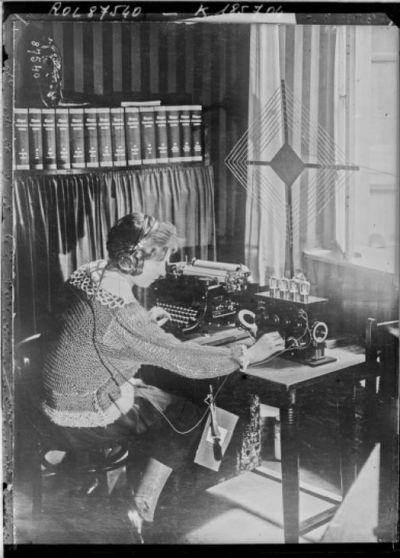 Concert par T.S.F. (Press photo) [femme tapant à la machine en écoutant la radio] : [photographie de presse] / [Agence Rol]