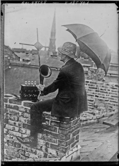 Concert par T.S.F., Press photo [homme écoutant la radio, assis sur le toit d'une maison] : [photographie de presse] / [Agence Rol]