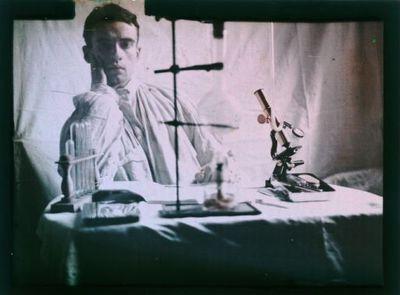 [Biologiste assis à sa table de travail] : [photographie] / [André Maret]