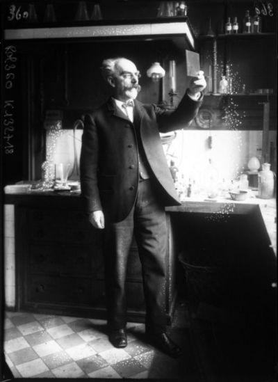 [M. Gabriel Lippmann, dans son laboratoire de la Sorbonne, regardant une plaque de verre] : [photographie de presse] / [Agence Rol]