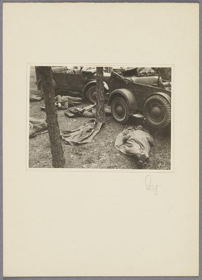 Soldaten schlafen vor Militärfahrzeugen