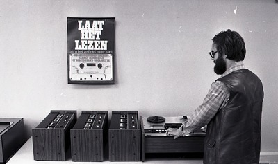 'De Band': een man staat achter een tape recorder; op de muur hangt een affiche me tekst 'Laat het lezen, als u het zelf niet meer kunt; de blindenbibliotheken hebben ieder           boek op geluidsband of cassette'.