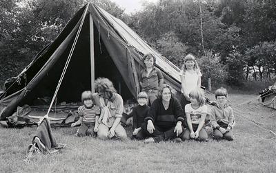 Jonge kinderen liggen en zitten met jeugdige begeleiders voor hun tent; over de scheerlijn hangt een deken. Weet iemand wie dit zijn, of dit padvinders of welpen betreffen           en ter gelegenheid waarvan deze foto is gemaakt?