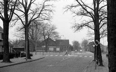 Wegen en verkeer: een voetganger gebruikt de zebra en passeert de verkeerszuil, gezien vanaf de Van Voorst tot Voorststraat. Op de andere hoek met de Maarten Trompstraat de           gebouwen van de gemeentelijke gasfabriek uit 1907.