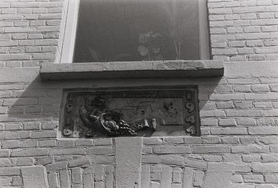 Met noesten vlijt vergaard - in zwaren strijd gespaard 1916 - 1944. Deze muurversiering is gemaakt door de Bossche beeldhouwer Kees van Valderen in 1944: een engel met een           hoorn van overvloed, op een banderol de initialen C.W. staande voor Caspar Wouters. Uit een overvliegend vliegtuig zijn twee parachutisten gevallen: symbool voor de           bevrijding