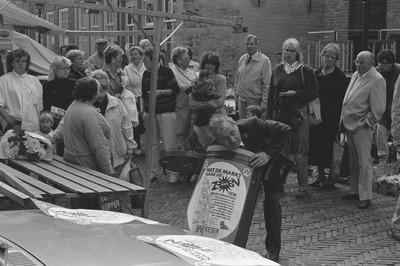 Verloting van prijzen op de markt met als tekst 'Keser, met de markt naar de zon toe'. De man die in de ton grabbelt is Piet Hendriks, gemeentebode en marktmeester. De man           rechts in het lichte pak met de hand in de broekzak is Toon van Gool. Weet iemand wie de rest zijn?