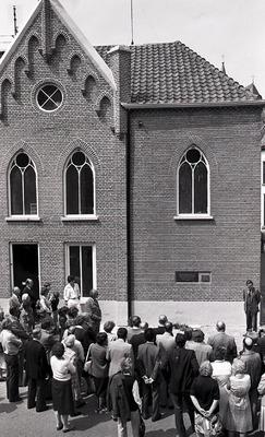 'In 1871 gebouwd als synagoge voor de Joodse Gemeenschap van Grave. Onder Duitse bezetting eindigde die bestemming en werd de tekst van deze steen afgeslagen. 16-5-1981'.           Een groep mensen heeft zich rond het gebouw verzameld.