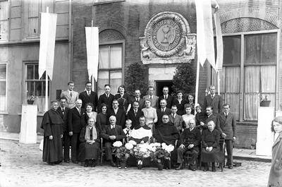 Een officiële bijeenkomst met vlaggen of vaandels; in de gevel van het gebouw staat de tekst: 'priester zijt gij in eeuwigheid'. Weet iemand wie dit zijn, waar dit is en ter           gelegenheid waarvan deze foto is gemaakt?