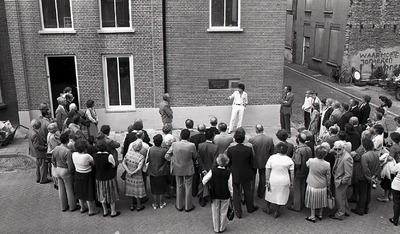 'In 1871 gebouwd als synagoge voor de Joodse Gemeenschap van Grave. Onder Duitse bezetting eindigde die bestemming en werd de tekst van deze steen afgeslagen. 16-5-1981',           een groep mensen staat rondom het gebouw.