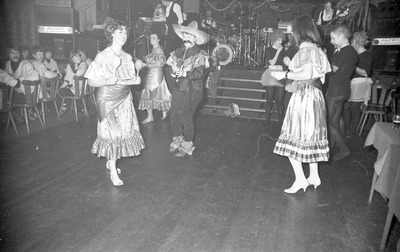Carnaval in Schijndel; Foto is waarschijnlijk gemaakt in De Lindeboom tijdens het Liekusfeest. Links op de achtergrond zitten de leden van carnavalsclub De Nachtravers (van           de Triangelbar). Helemaal links zit Frans Huibregts, daarlangs Johnny Vissers; Helemaal rechts op de stoel zit Dorus van Heeswijk. Het optreden is van CV De Broekhoesters.