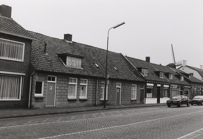 Dorpswoningen. Gebouwd in ca. 1870. Verbouwing ca. 1970. Het huis geheel links half zichtbaar werd onder meer bewoond door de familie Van Boxtel. Rechts daarvan woonde Kees           van Bakel. Weer rechts bij het Marlboro-bord was een winkel van de familie Van Bokhoven.