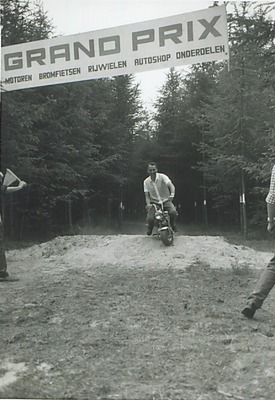 Een man op een mini-motor passeert een kleine heuvel; op de achtergrond hangt een spandoek 'Grand Prix'. Weet iemand wie dit is en ter gelegenheid waarvan deze foto is           gemaakt?