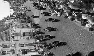 Er zijn veel bezoekers op straat bij de kruising van de Hamstraat; leden van het Gilde passeren het pand van de Poort van Cleve. Weet iemand waar dit is en ter gelegenheid           waarvan deze foto is gemaakt?