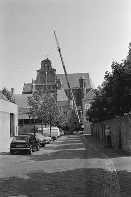 Een kraan staat bij de kerk; vanaf een bak worden werkzaamheden verricht, gezien vanuit een zijstraat. De kraan is van de firma Van Grinsven B.V. Weet iemand ter gelegenheid           waarvan deze foto is gemaakt?