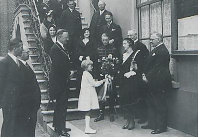 Een meisje biedt een bos bloemen aan; achter haar staat burgemeester Ficq en een aantal vrouwen op de trap van het raadhuis. Weet iemand wie dit zijn en ter gelegenheid           waarvan deze foto is gemaakt?