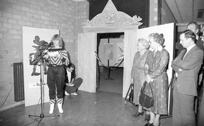 Voordracht, waarschijnlijk t.g.v. de opening van een tentoonstelling (tijdens de Pasar Malam?). We zien voornamelijk docenten van de voormalige MAVO, later Eldecollege.           Gehurkt: Aernout Konijnenberg (geen docent), geheel rechts: Piet Creemers (directeur), achter Piet: Theo van Heijningen (bio/nat/schei), tweede van rechts: Mimi Verhoeven (en). Weet iemand           meer?