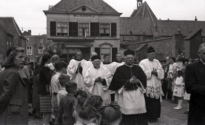 Religie: een processie verlaat een kerkgebouw; rooms katholieke geestelijken hebben de handen gevouwen; op de achtergrond het pand van de slagerij. Weet iemand wie dit zijn           en ter gelegenheid waarvan deze foto is gemaakt?