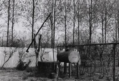 Landbouwperceel met enkele voorwerpen die als in een openluchtmuseum te zien zijn: (een metalen sopketel onder een stenen afdak, een hooiberg van het type eenroedenberg en)           hier een bakstenen waterput met putmik.